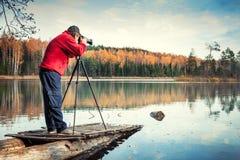 Fotografo dell'uomo con la macchina fotografica su un pilastro Fotografia Stock