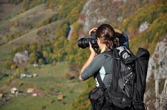 Fotografo della donna che prende una foto nelle montagne all'autunno Fotografia Stock