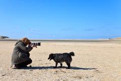 Fotografo della donna nelle dune di sabbia sulla spiaggia Immagini Stock