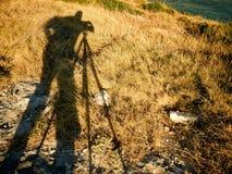 Fotografo della siluetta che prende la spiaggia del treppiede del colpo Fotografia Stock
