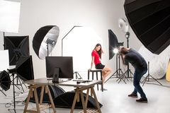 Fotografo e modello grazioso che lavorano nello studio moderno di illuminazione immagini stock