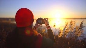 Fotografo femminile che fotografa, ragazza del viaggiatore teenager turistico della ragazza che fa foto del lago della spiaggia D stock footage