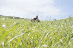 Fotografo Hiding di appostamenti nell'erba fotografia stock
