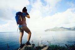 fotografo Hiking In Seaside che prende foto con la macchina fotografica fotografie stock