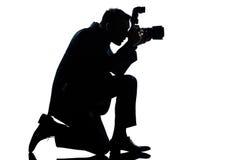 Fotografo inginocchiato dell'uomo della siluetta Fotografia Stock