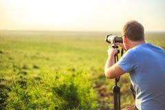 Fotografo professionista che prende foto sulla savana Fotografia Stock