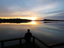 Fotografo professionista Silhouette con il treppiede durante il tramonto sopra il bello lago con il cielo nuvoloso nel fondo fotografia stock