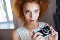 Fotografo riccio della giovane donna della bella testarossa con la macchina fotografica d'annata Fotografia Stock