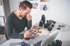 Fotografo stancato che si siede alla tavola fotografia stock