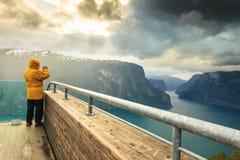 Fotografo turistico con la macchina fotografica sull'allerta di Stegastein, Norvegia Immagine Stock