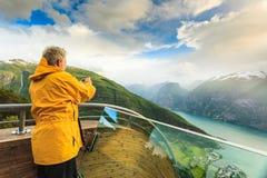 Fotografo turistico con la macchina fotografica sull'allerta di Stegastein, Norvegia Immagini Stock