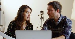 Fotografowie dyskutuje nad laptopem przy biurkiem 4k zdjęcie wideo