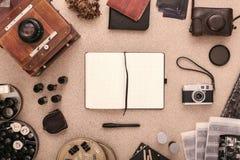 Fotografs skrivbord med den öppna urklippsboken, tappningkameror och rullar av filmen Lekmanna- lägenhet royaltyfri foto