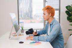 Fotografsammanträde på skrivbordet som retuscherar nya foto i hans studio Royaltyfri Bild