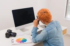 Fotografsammanträde på skrivbordet som retuscherar nya foto i hans studio Royaltyfria Foton