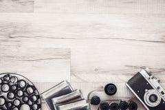 Fotografschreibtisch mit Weinlesekamera und -Filmrollen Flache Lage mit Kopienraum Stockbilder