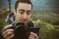 Fotografskytte utanför med den digitala kameran Arkivfoto