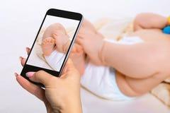 Fotografujący dziecka pojęcie - cieki sześć miesięcy stary dziecko jest ubranym pieluszki Zdjęcia Royalty Free