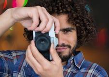 Fotografvordergrund, der ein Foto mit Weinlesekamera macht Unscharfe blaue Stadt beleuchtet Hintergrund Stockfoto