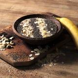 Fotographia dell'alimento Frullato della frutta su un piatto di legno Dadi e papavero delle banane fotografia stock libera da diritti