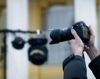 Fotogrf на деятельности для того чтобы сделать успешное фото, оно поднимает камеру вверх стоковое фото