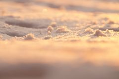 Fotohintergrund, Makroschnee im Sonnenunterganglicht Unscharfes Goldenes und Lizenzfreie Stockbilder