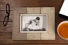 Fotokader, citroenthee en mobiele telefoon op houten plank royalty-vrije stock afbeeldingen