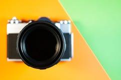 Fotokamera på orange och grön bakgrund arkivbild