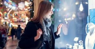 Fotokant van jong brunette bij winkelvenster in avond royalty-vrije stock afbeelding