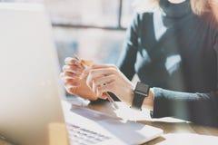 Fotokvinna som arbetar det moderna kontoret Flicka som bär den generiska designSmart klockan Kvinnliga händer som rymmer blyertsp Arkivfoto