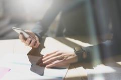 Fotokvinna som arbetar det moderna kontoret Flicka som bär den generiska designSmart klockan Kvinnliga hållande smartphonehänder  Royaltyfria Bilder