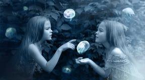 Fotomanipulatie in blauw met meisjes en kwallen Stock Foto's