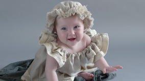 Fotoperioden av den lilla flickan i huvudbonad och klänning sitter, i träask och att posera på kamera stock video