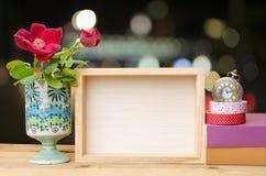 Fotorahmen mit Büchern und Blumen auf dem Holztisch auf bokeh Hintergrund Lizenzfreie Stockfotografie