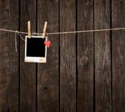 Fotorahmen mit Papierherzfall auf Seil Stockbild