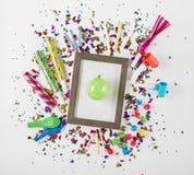 Fotorahmen mit Parteikonfettis, -ballonen, -krachmachern und -dekor Stockfoto