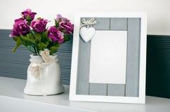 Fotorahmen steht auf einem Regal nahe bei den Blumen Lizenzfreies Stockbild