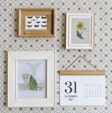 Fotorahmen und -kalender gehangen an Wand Lizenzfreie Stockfotos