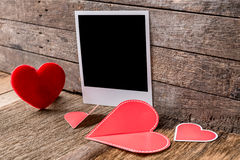 Fotorahmen- und -Valentinsgrußtagesherz über hölzernem Hintergrund Stockfoto
