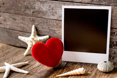 Fotorahmen- und -Valentinsgrußtagesherz über hölzernem Hintergrund Stockfotos