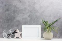 Fotoramåtlöje upp med växter i vas, keramisk stjärna, penna och blyertspenna i murarekrus på hylla Skandinavisk stil arkivbild