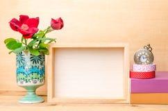 Fotoram med böcker och blommor på trätabellen Royaltyfri Foto