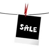 Fotoram med försäljningsmeddelandet på en klädstreck Arkivbild