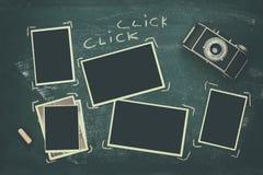 fotoramar bredvid gammal kamera över svart tavla Fotografering för Bildbyråer