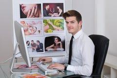 Fotoredacteur die laptop met behulp van bij bureau Royalty-vrije Stock Foto