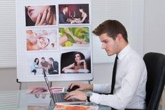 Fotoredacteur die laptop met behulp van bij bureau royalty-vrije stock fotografie