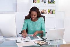 Fotoredaktör som arbetar på kontorsskrivbordet Fotografering för Bildbyråer