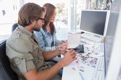 Fotoredaktörer som tillsammans arbetar på skrivbordet Royaltyfria Bilder