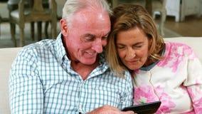 Fotos capturadas de repaso sonrientes de los pares mayores en el teléfono móvil en sala de estar almacen de metraje de vídeo