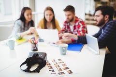 Fotos con las auriculares de la realidad virtual en la tabla contra editores de fotos Fotografía de archivo